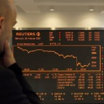 A man looks on a display of the Swiss Market Index SMI at the Swiss Exchange in Zurich