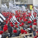 A man waves a traditional black Breton hat as protesters with Brittany regional flags and wearing red caps, the symbol of protest in the region, take part in a demonstration to maintain jobs in Quimper